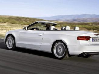Ein weißes Audi A5 Cabrio fährt durch eine Wüstenlandschaft.