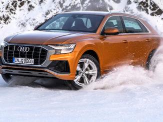 Audi Q8 anno 2018, Fahraufnahme durch den Schnee, Farbe: Drachenorange