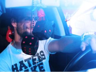 Ein junger Mann sitzt zufrieden am Steuer seines Autos.
