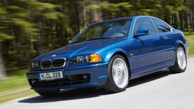 Ein blauer BMW 3er (E46 Coupé) fährt auf einer Landstraße am Waldrand.