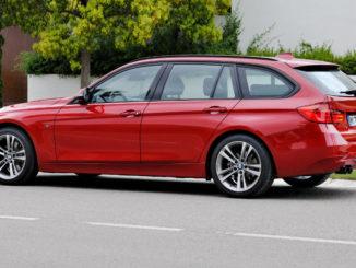 Ein roter BMW 3er Touring steht 2012 vor einer Stadtvilla.