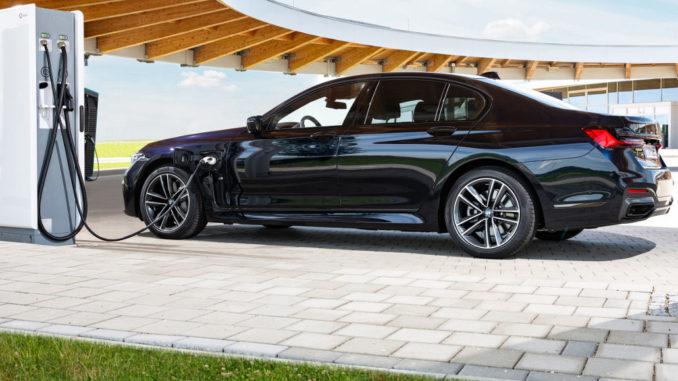Ein blauer BMW 745e Plugin_hybrid steht 2020 an einer Ladesäule.