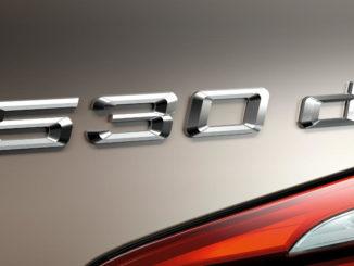 Typenschild eines BMW 5er Touring (03/2010) vor beigem Hintergrund.
