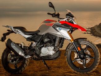 BMW Ein rot-silbernes BMW-Motorrad vom Typ G 310 GS (01/2017) steht vor einem Küstenpanorama bei Abenddämmerung.
