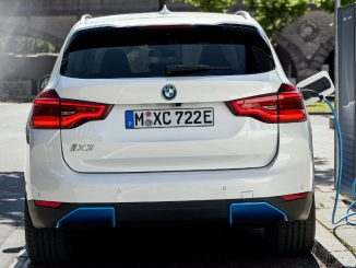 Ein weißer BMW iX3 steht im Sommer 2020 an einer Ladesäule in München.