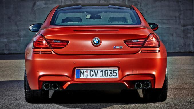 Das neue BMW M6 Coupé in Orange steht vor einer Betonwand (12/2014).