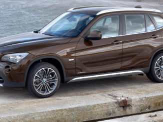 Ein brauner BMW X1 (E84) steht 2009 auf einer Hafenmole.