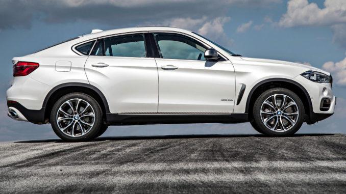 Ein weißer BMW X6 xDrive50i (F16 von 10/2014) aufgenommen im Profil steht auf einer Asphaltfläche mit Reifenspuren.