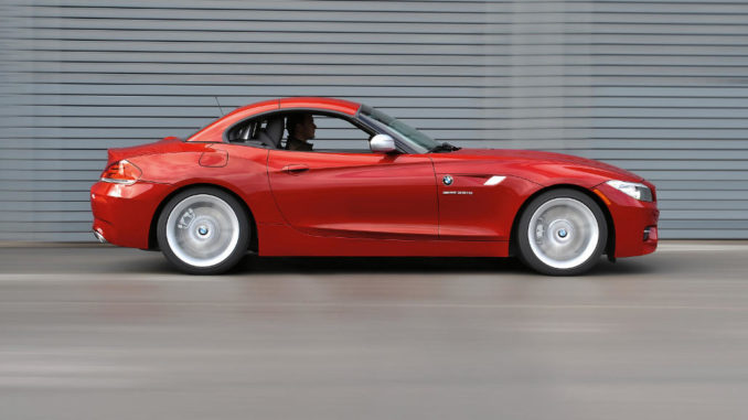 Ein roter BMW Z4 sDrive35is (11/2009) fährt dicht an einer Lärmschutzwand entlang.