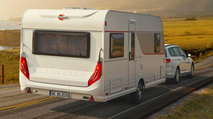 Ein Auto zieht 2020 einen Wohnwagen vom Typ Bürstner Averso über eine Küstenstraße.