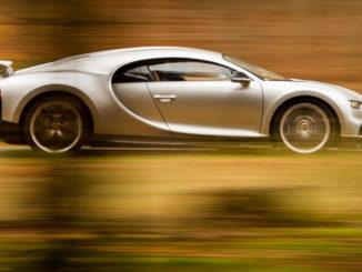Ein silberner Bugatti Ciron fährt durch einen herbstlichen Wald.