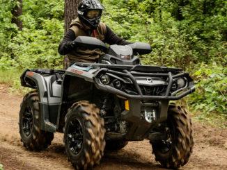 Ein ATV Can-Am Outlander fährt auf einem Waldweg.