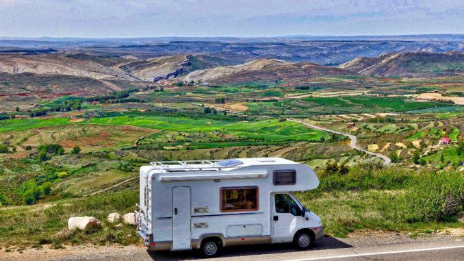 Wohnmobil am Straßenrand vor einem grünen Tal.