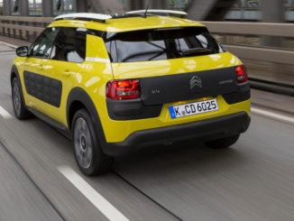 Ein gelber Citroen C4 Cactus fährt über ein Brücke.