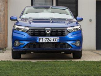 Ein blauer Dacia Sandero, Fünftürer, steht 2020 vor einem Reihenhaus.