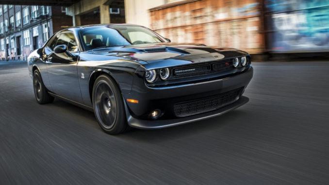 Ein schwarzer Dodge Challenger fährt auf einer Straße einer US-amerikanischen Stadt.