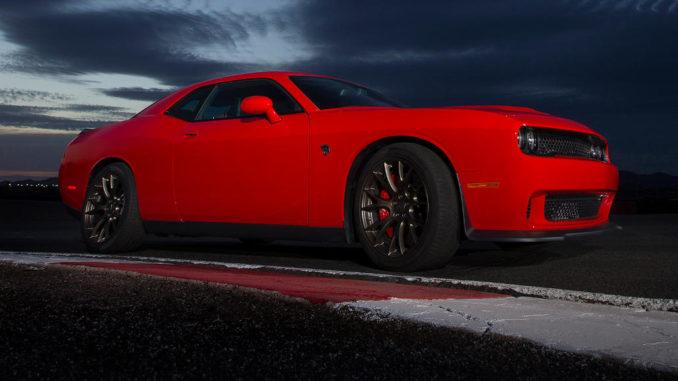 Ein roter Dodge Challenger SRT fährt 2017 bei Dämmerung auf einer Rennstrecke.