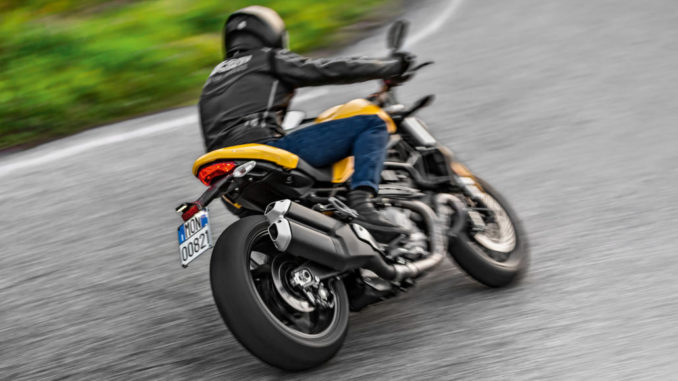 Der Fahrer einer gelben Ducati Monster 821 legt sich 2017 auf einer Landstraße in die Kurve.