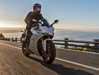 Eine weiße Ducati SuperSport fährt bei Sonnenaufgang auf einer Küstenstraße - PRESS TEST 2017