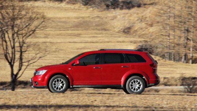 Ein roter Fiat Freemont fährt durch herbstliches Gelände.