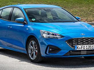 Ein blauer Ford Focus der vierten Generation steht 2018 vor einem Grashügel.