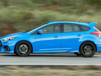 Ein blauer Ford Focus RS rast 2015 auf einer Landstraße entlang.
