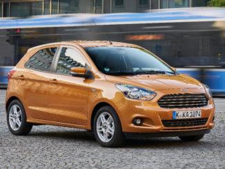 Ein bronze-farbener Ford Ka+ steht 2016 auf einem Platz in München, an dem eine Trambahn vorbeifährt.
