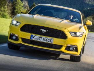 Ein gelber Ford Mustang fährt 2015 durch die Voralpenlandschaft.Mehr als 10.000 Ford Mustang haben Kunden europaweit seit Ende 2014 bestellt. Im Dezember des vergangenen Jahres waren die Auftragsbücher für den Sportwagen geöffnet worden.