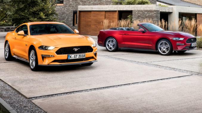 Ein oragenes Ford Mustang Coupé und ein rotes Cabrio stehen 2017 vor einer Villa.