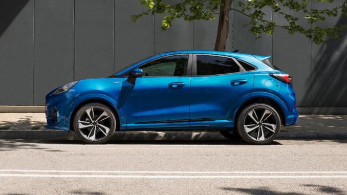 Ein blauer Ford Puma steht 2019 am Straßenrand vor einem Baum.