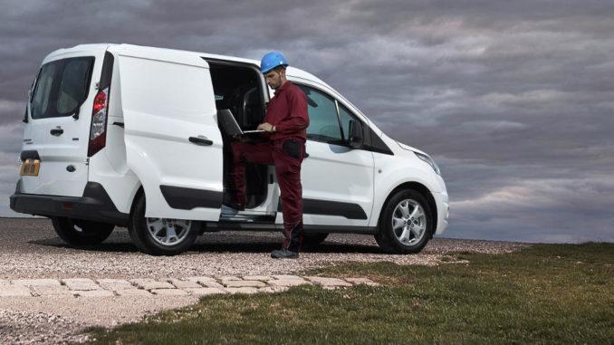 Ein Bauarbeiter mit Laptop steht 2013 vor einem weißen Ford Transit Connect mit geöffneter Seitentür