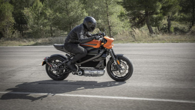 Eine orangene Harley-Davidson Livewire fährt 2020 auf einer Landstraße am Waldrand.
