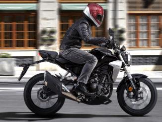 Eine schwarze Honda CB300R fährt 2017 an einem älteren Bürogebäude vorbei.