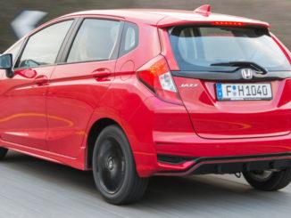 Ein roter Honda Jazz fährt eine Landstraße bergauf (Images of 2018 Jazz Dynamic 1.5-litre i-VTEC).