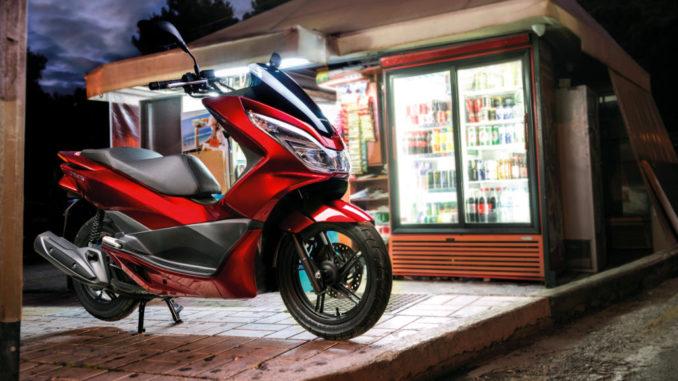 Eine rote Honda PCX125 steht abends vor einem Kiosk.