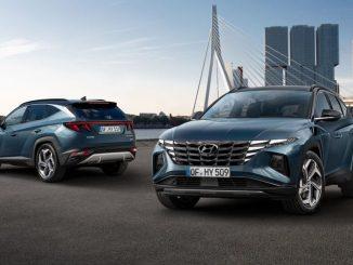 Zwei blaue Hyundai Tucson stehen 2020 vor einer Großstadtshilouette.