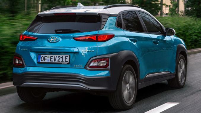 Ein türkiser Hyundai Kona Electric fährt 2018 auf einer Straße durch die Stadt.