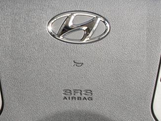Lenkrad mit Hyundai-Logo, Hupen- und Airbag-Symbol in Großaufnahme.
