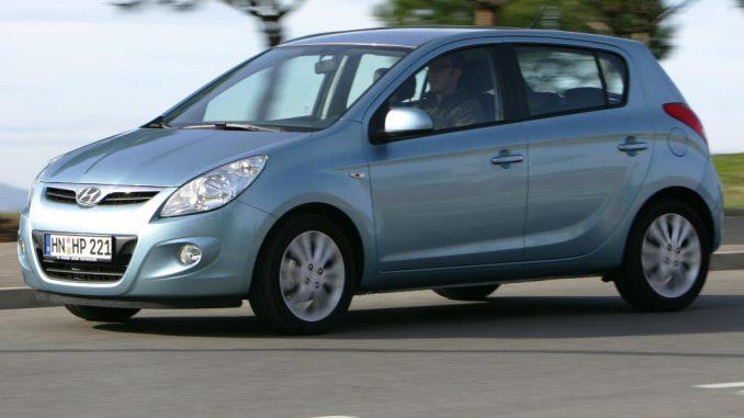 Ein silberner Hyundai i20 fährt 2009 an Pinien vorbei.