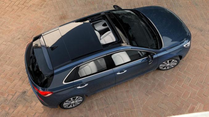Ein blauer Hyundai i30 steht mit geöffnetem Schiebedach auf einer gepflasterten Fläche.