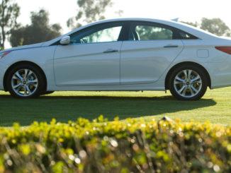Ein weißer Hyundai Sonata des Modelljahres 2011 steht auf einer Rasenfläche.