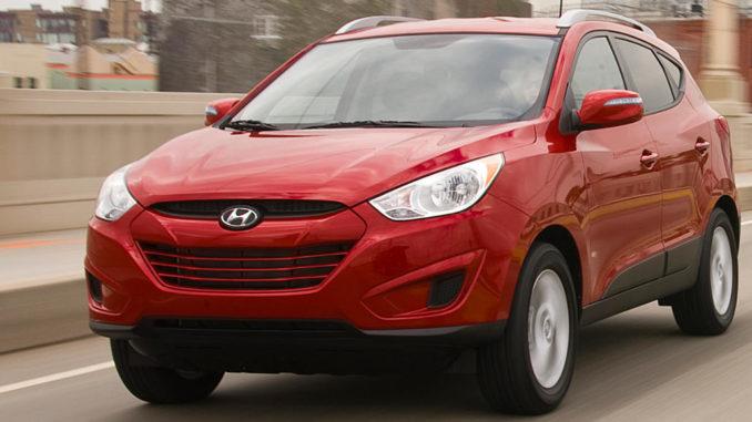 Ein roter Hyundai Tucson fährt 2012 über eine Brück einer amerikanischen Großstadt.