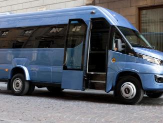 Ein blauer Iveco Daily Minibus steht vor einem Hotel.