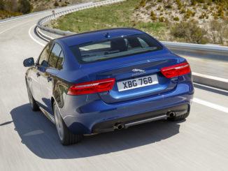 Ein blauer Jaguar XE fährt 2016 auf einer Landtstraße-