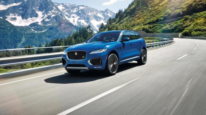 Ein blauer Jaguar F-Pace fährt durch eine Berglandschaft.