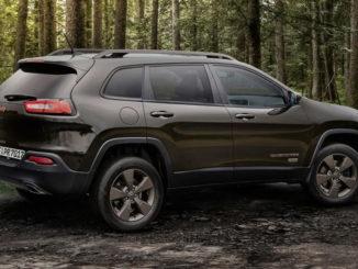 Ein brauner Jeep Cherokee 75th Anniversary steht 2016 auf einer Waldlichtung.