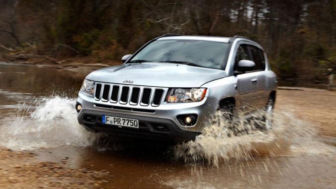 Ein silberner Jeep Compass fährt durch ein Flussbett