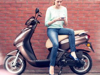 Ein junge Frau sitzt auf einem Roller Peugeot Kisbee