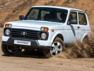 Ein weißer Lada 4x4 Urban fährt durch den Sand einer Kiesgrube.