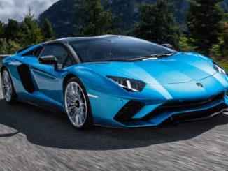 Ein blauer Lamborghini Aventador S Roadster fährt mit geschlossenem Dach auf einer Bergstraße.
